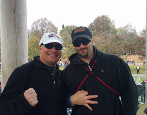 Mark Sahady posing outside with another man. Mark wears a white American flag baseball cap and sunglasses and is smiling. His right hand is held up in a fist. The other man wears a blue American flag baseball cap and sunglasses and holds his hand up in the okay sign.