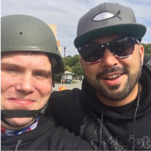 """Photo of John Camden wth Joey Gibson, Camden in black and wearing a gray helment, Gibson in black and sunglasses wearing a baseball hat with an ichthys or """"Jesus fish"""" symbol."""
