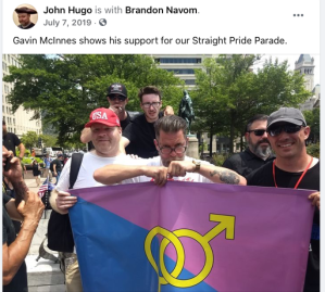"Screenshot of Facebook post from July 7, 2019 by John Hugo who tags Brandon Navom. Image is of Hugo, Navom, and Gavin McInnes holding up a ""straight pride"" flag. Text of post reads ""Gavin McInnes shows his support for our Straight Pride Parade."