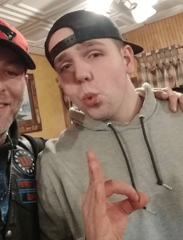 """Michael Moura in a hoodie and backwards baseball hat makes the """"okay"""" hand gesture. Appears to be in a function hall or restaurant and posing with another man in a leather jacket who is mostly off camera."""