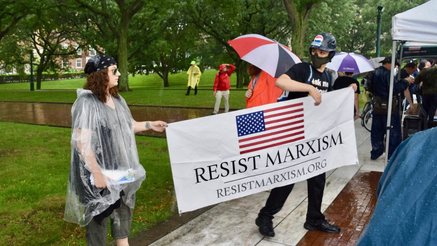 """Photo of a gathering of people in a park. Two white people in foreground, one in helmet and face mask, hold up a banner with United States flag and the text """"Resist Marxism, resistmarxism.org."""""""
