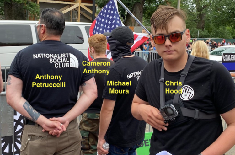 "Photograph of man in sunglasses, a Nationalist Social Club shirt, and with a Go Pro strapped to his chest facing the camera and 3 men dressed in black facing away. Man facing the camera is labelled Chris Hood and other 3 are labelled, left to right, Anthony Petruccelli, Cameron Anthony, and Michael Moura. Petruccelli wears a shirt that reads ""Nationalist Social Club"" next to what looks like a North Face logo. Police barricades and a crowd are in the background."
