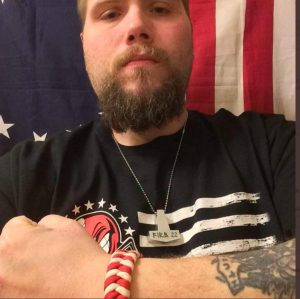 """Photo of a bearded John Camden in front of a US flag. Camden is posing and wearing a necklace shaped like Thor's hammer reading """"Firm 22"""" in faux runes, a reference to the racist Vinlanders Social Club gang."""