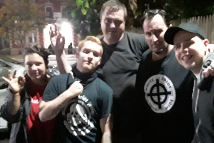 """Blurry group photo of 5 white men, mostly dressed in black, at night. Two making the """"okay"""" hand gesture. One has a shirt that reads """"white pride world wide"""" and another in a skull shirt that appears to read """"Patriot Front"""""""