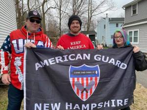 """Photo of John Camden in """"USA"""" hoodie and two other people, one in Trump shirt stand outside holding up flag reading """"American Guard New Hampshire"""" with the American Guard logo. That log is a red white and blue shield with a cannon reading """"com and take it"""" and two crossed butcher's cleavers."""
