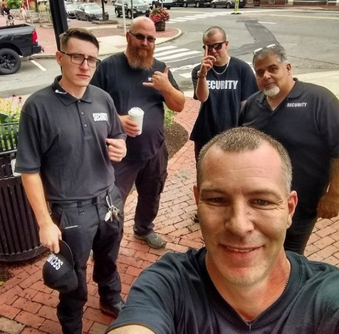 """Photo of a man with short cropped greying hair taking a selfie on a sidewalk with 4 other men in the background. All dressed in black with """"security"""" shirts on"""