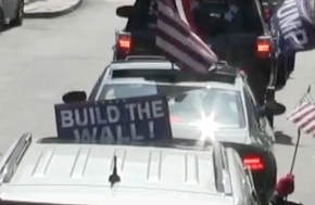 "Photo of line of cars in a procession, lots of US flags visible long with a Trump flag and a ""Build the Wall"" sign."