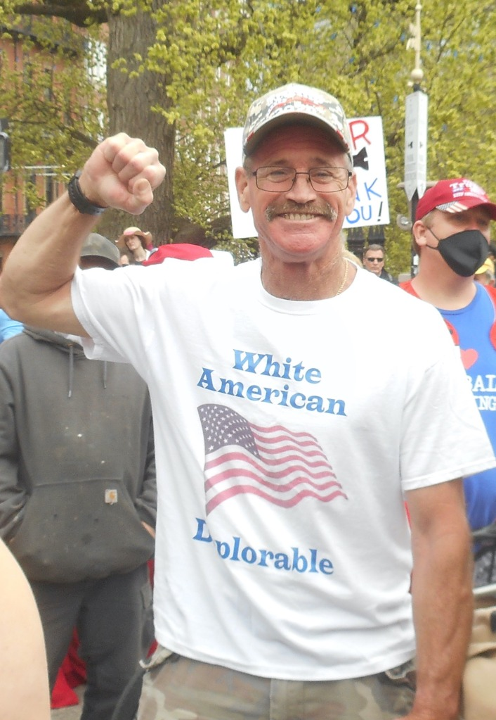 "Man with mustache and classes raises fist at a rally. White shirt has a US flag an dreads ""White American Deplorable"""
