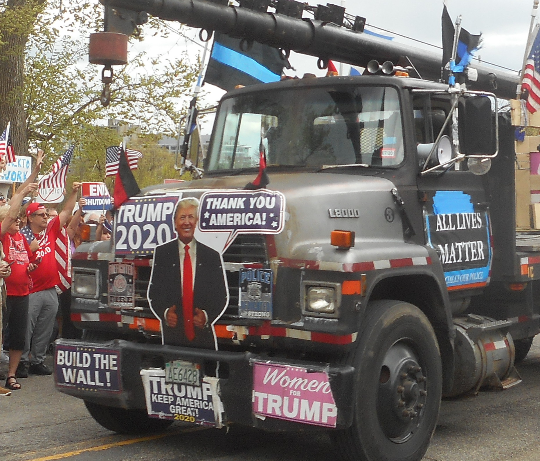 """Photo of large black truck with crane. Crowd in red with US flags raise their fists at in in the background. Truck is coerd in Trump signs including a cutout of Trump, """"Build the Wall,"""" """"Trump 2020"""" """"Women for Trump,"""" """"All Lives Matter,"""" and thin blue line flags."""