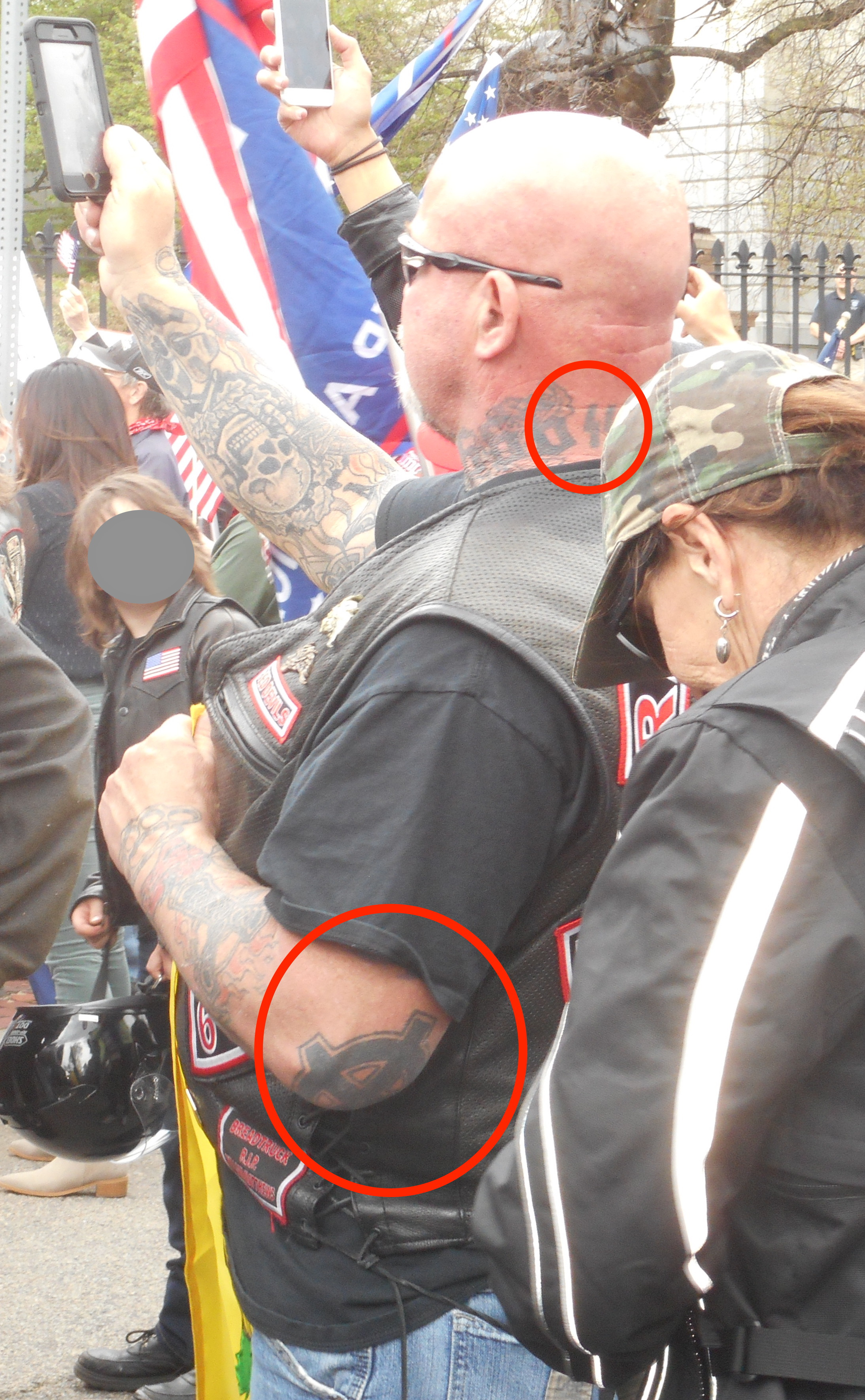 "Bald man with leather biker vest at a rally. Man has many tattoos and red circles point out a Nazi ""SS"" bolt neck tattoo and the white supremacist version of the rounded Celtic cross on his left elbow."