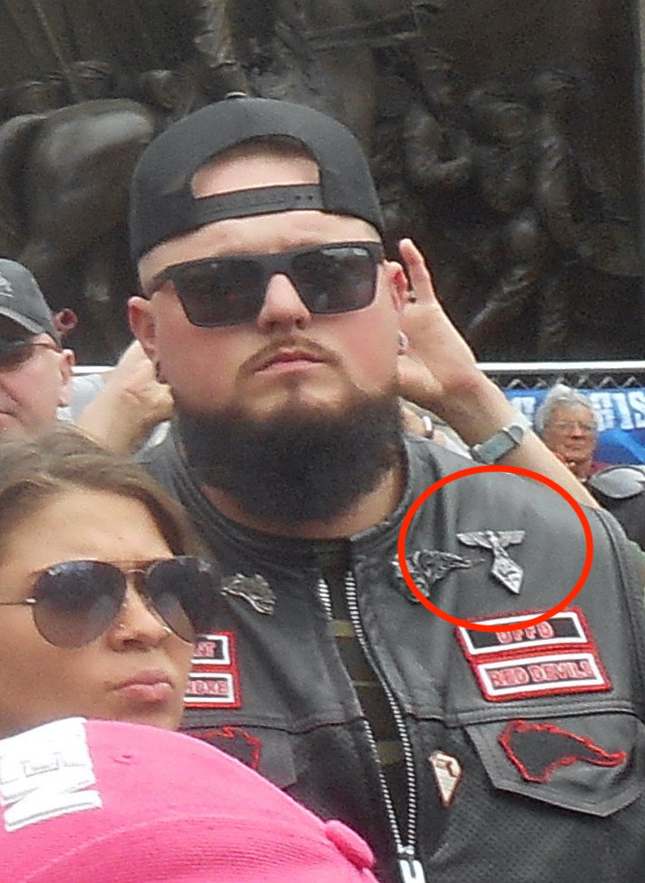 Beared man in a black baseball hat an suglasses in a crowd. Leather jacket has a Nazi eagle emblem pin on it, highlighted by a red circle.