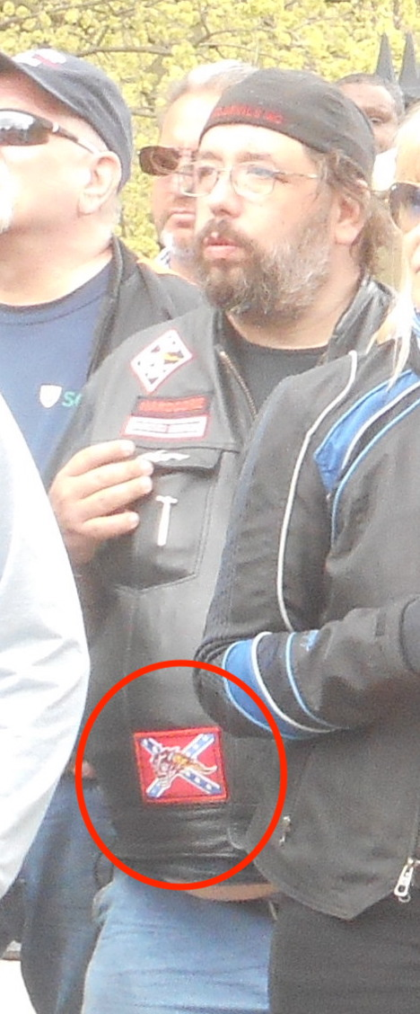 Image of a beared man in a crowd with a leather jacket with a Confederate flag patch on it. Patch is indicated with red circle.