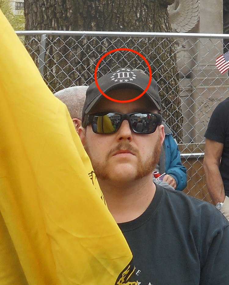 Photo of a man with muttonchops in sunglasses and black 3 percenter baseball hat. Logo is pointed out with red circle. Appears to be behind a Gadsden flag.