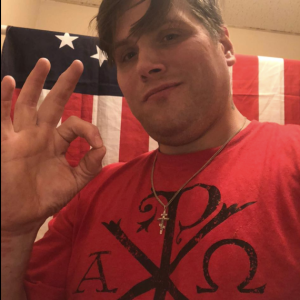 """Picture of John Camden in front of a US flag making the """"okay"""" hand gesture. Wears a cross necklace"""